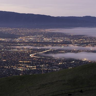 A early morning fog rolls into San Jose Calif. Typical late summer, early fall morning. The heat in the Central Valley pulls the fog in through the Golden Gate overnight and the fog slowly makes its way up valley covering the city for the morning commute. The I680 corridor is seen as the bending line of lights near the center of the picture.