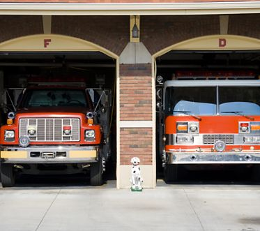 Two fire trucks in the bays at the fire station