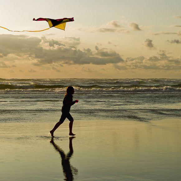A girl flies a kite near sunset on the beach in Newport, Oregon.