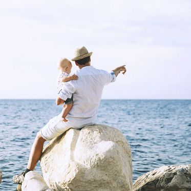 Father with daughter on sea and sky backgrounds. Man and baby are point out forward. Parent and child together at summer. Family, Lifestyle, Holidays and Travel concept. Piran, Slovenia, Europe