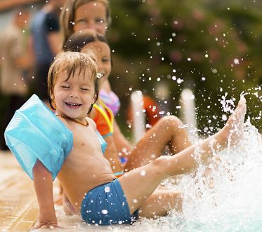 Kids in swimming pool have fun and splashing water