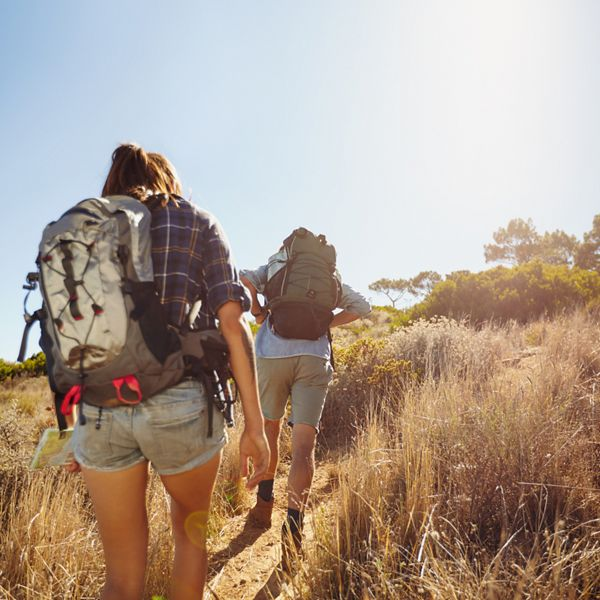 Rear view image of two young people carrying backpacks walking through mountain trial on summer day. Man and woman hiking on bright sunny day.