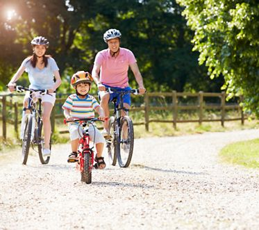 Asian Family On Cycle Ride In Countryside Cycling Towards Camera