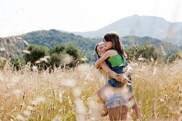 Girl carrying friend in field