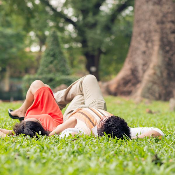 Close up image of a senior couple lying on the grass in the park