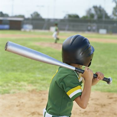 side profile of a boy swinging a baseball bat