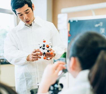 Teacher explaining molecules in Junior High school Science Lab using glucose molecular model and microscopes