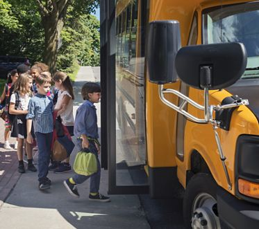 Stock Image of children boarding a school bus - Woodbury Court Apartment Homes, Irvine, CA