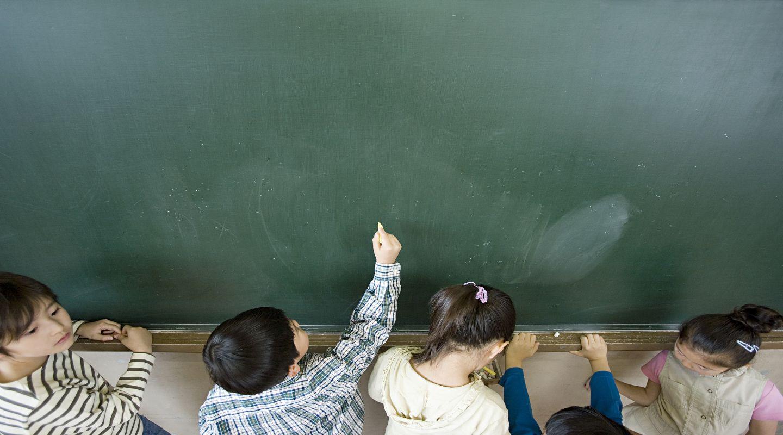 A boy writing on a blackboard