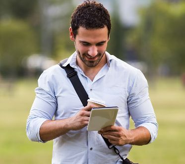 Young businessman is drinking coffee and using digital tablet at the park.