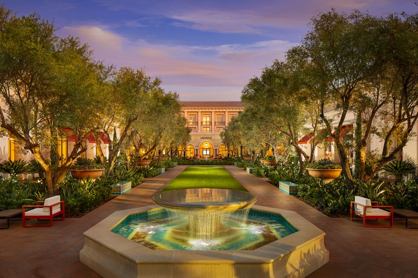 Exterior view of courtyard with fountain at Promenade Apartment Homes in Irvine, CA.