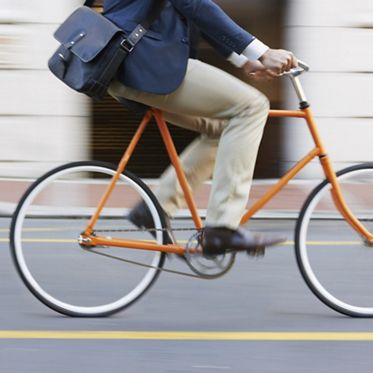 Cropped shot of a man riding his bicycle through the city