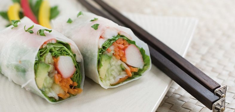 Two hand rolled temaki style sushi rolls filled with vegetables, surimi and ebi.  Shallow dof.