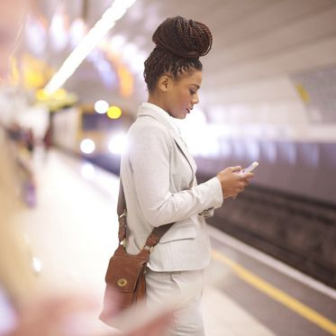 A young businesswoman is standing at an underground subway station checking her phone. In the background a tube train is approaching with it's lights lighting the inside of the tube . In the foreground another woman is shown defocussed .